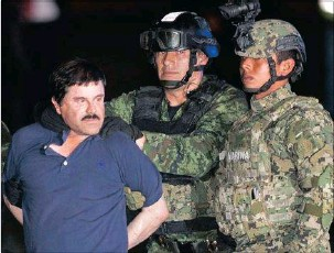 """?? PICTURE: AP ?? CAUGHT: Joaquin """"El Chapo"""" Guzman is escorted to a helicopter in handcuffs by Mexican soldiers and marines in Mexico City on Friday. Guzman was recaptured six months after escaping from a maximum security prison."""