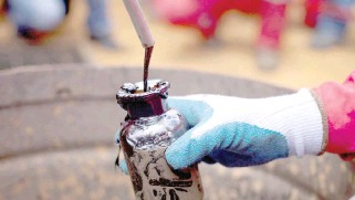 ?? ?? A worker collects a crude oil sample at an oil well operated by Venezuela's state oil company PDVSA in Morichal.