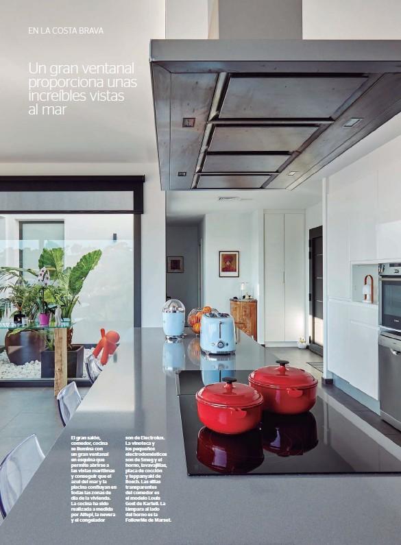 ??  ?? El gran salón, comedor, cocina se ilumina con un gran ventanal en esquina que permite abrirse a las vistas marítimas y conseguir que el azul del mar y la piscina confluyan en todas las zonas de día de la vivienda. La cocina ha sido realizada a medida por Alfepi, la nevera y el congelador son de Electrolux. La vinoteca y los pequeños electrodomésticos son de Smeg y el horno, lavavajillas, placa de cocción y teppanyaki de Bosch. Las sillas transparentes del comedor es el modelo Louis Gost de Kartell. La lámpara al lado del horno es la FollowMe de Marset.
