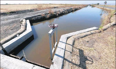 ?? Rich Pedroncelli Associated Press ?? WATER flows down a canal near Byron, Calif. Regulators are proposing a $ 1.5- million fine against the Byron- Bethany Irrigation District.