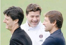 ?? — AFP ?? Paris Saint-germain's head coach Mauricio Pochettino (C) jokes with sporting director Leonardo (R) and deputy sporting director Angelo Castellazzi (L) during a training session.