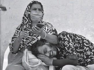 ??  ?? Un jeune homme pleure la mort de son père à cause de la Covid-19, à Ahmedabad (Inde)