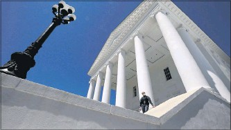 ?? BOB BROWN/TIMES-DISPATCH ?? A Capitol Police officer stood on the steps of the Virginia State Capitol in April during the legislative veto session. Members of the House of Delegates met outside in a tent instead of the chamber because of the coronavirus pandemic.