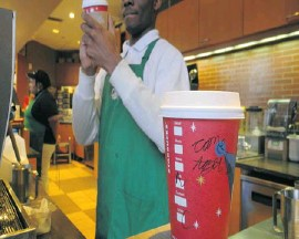 "?? EVA HAM­BACH/AFP/GETTY IM­AGES ?? A Star­bucks barista fol­lows the com­pany's re­quest to write ""come to­gether"" on cups to pres­sure law­mak­ers to com­pro­mise on a deal to avert a year-end fis­cal cri­sis."