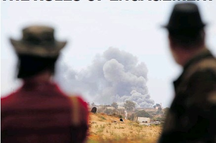 ?? ASMAA WAGUIH, REUTERS ?? Anti-gadhafi fighters look on as smoke is seen from an explosion during heavy shelling and clashes with Gadhafi forces in Sirte on Oct. 7, 2011.