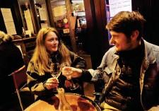 ??  ?? Paris (XIIIE), hier. Pour Chloé et César, venus profiter des dernières heures de liberté dans les cafés de la Butte-aux-cailles (à dr.), cette soirée a une saveur de « reconfinement », voire d'« on recommence tout ».