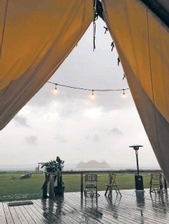 ?? PHOTO BY LAURA MARTIN ?? The Staten Island Ferry looms out of a rain squall, with the drenched outdoor dining area of the campsite in the foreground.