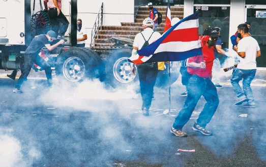 ?? EZEQUIEL BECERRA/AGENCE FRANCE-PRESSE/GETTY IMAGES ?? Tear gas engulfs protesters in Costa Rica in October after the government proposed broad tax increases to boost its bid for a $1.75 billion bailout from the IMF.