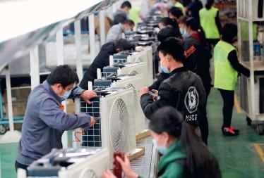 ??  ?? Le 16 mars 2020, sur la ligne de production de climatiseurs de la société TCL, située dans la zone portuaire de Chengxi à Jiujiang (Jiangxi), des ouvriers assemblent des climatiseurs destinés à l'exportation vers l'Europe.