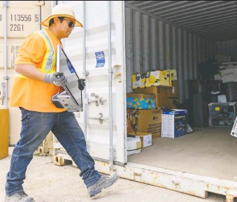 ?? AZIN GHAFFARI ?? Tenzin Rangdol, an employee at Recycle Logic, moves electronic wastes brought to the electronic recycle depot to a storage container on Tuesday.