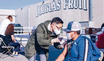 ?? JENNIFER KING Tri-city Herald ?? Pharmacist Johnny Nguyen administers a dose of the COVID-19 vaccine to a Douglas Fruit worker Friday during a pop-up clinic outside of the company's Pasco facility. The agricultural producer partnered with the Washington State Tree Fruit Association and Safeway/albertsons to administer Johnson & Johnson's Janssen single-dose vaccine to employees.