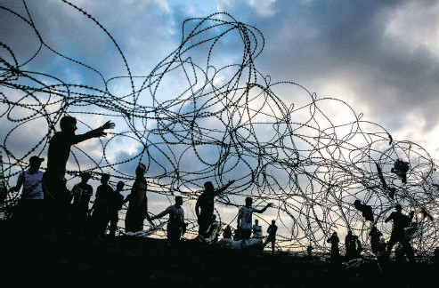 ?? MOHAMMED ABED / AFP / GETTY IMAGES ?? Palestinian protesters near a barbed-wire fence along the border with Israel in the central Gaza Strip on Friday.