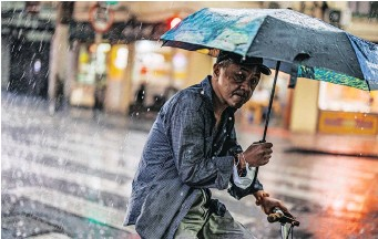 ??  ?? A MAN rides a bicycle in the rain in Shanghai, China, yesterday. China's population on the mainland reached 1 411 78 billion, growing 0.53% on average annually in the past decade, accord to the National Bureau of Statistics.   EPA
