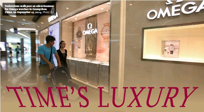 ??  ?? Pedestrians walk past an advertisement for Omega watches in Guangzhou, China, on September 27, 2014.