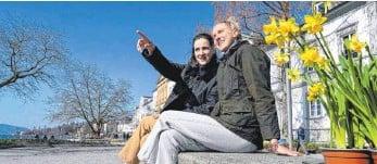 ?? FOTO: FELIX KÄSTLE/DPA ?? Zwei Studentinnen sitzen neben ihren gerade eben gekauften Osterglocken an der Uferpromenade in Überlingen – einem Ort zum Verweilen.