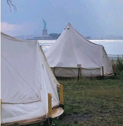 ?? ROBIN MARTIN/THE NEW MEXICAN ?? The Statue of Liberty is visible beyond the campsite's canvas tents as a rain shower pelts the New Jersey shore in the background.