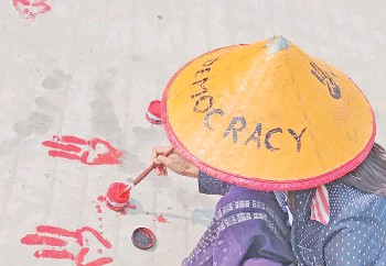 ?? — AFP photos ?? A protester painting the symbols of the three finger salutes on the ground with red paint in Shwebo in Sagaing region.
