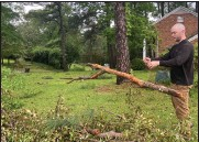 ?? (AP/The Meridian Star/Anne Snabes) ?? Nick Nissen picks up debris at his home Wednesday in Meridian, Miss., after Tuesday's storms and heavy rain.