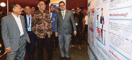 ?? PIC BY SALHANI IBRAHIM ?? Communications and Multimedia Minister Datuk Seri Salleh Said Keruak (third from left), Malaysian Communications and Multimedia Commission chairman Tan Sri Dr Halim Shafie (left) and other officials at the Malaysia FinTech Expo 2018 in Kuala Lumpur...