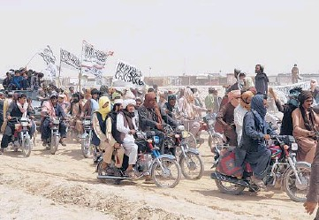 ?? TARIQ ACHKZAI/AP ?? Taliban supporters carry their signature white flags July 14 after the Taliban said they seized the Afghan border town of Spin Boldak across from Chaman, Pakistan. The Taliban want President Ashraf Ghani removed from office.
