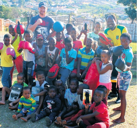 ??  ?? Heavyweight fighter Joshua Pretorius and community leader Wiseman Mthiyane (back) with a group of excited aspirant young boxers at the handover Richard Springorum