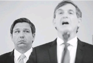 ?? BRYNNANDERSON/AP ?? Gov. RonDeSantis, left, listens to Florida Surgeon General Dr. Scott Rivkees speak about theCOVID-19 virus at a news conference March 2 at the FloridaDepartment ofHealth in Miami. The surgeon general largely disappeared frompublic viewafter a news conference inApril where he said social distancing practices could be necessary for another year— a statement at odds withDeSantis'message on the disease.