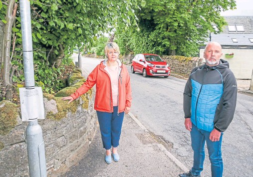 ??  ?? AN­NOYED: Frances MacGruer and Dun­can Chisholm of Muir of Ord Com­mu­nity Coun­cil at the Black Isle road junc­tion in Muir of Ord