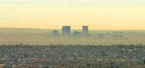 ?? RJ Sangosti, Denver Post file ?? A brown cloud surrounds Denver in this file photo. Oil and gas regulators have proposed rules that aim to improve air quality in the state.