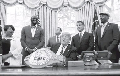 ?? OLIVIER DOULIERY/BLOOMBERG ?? Boxers Lennox Lewis, right, and Deontay Wilder, second from left, joined Sylvester Stallone at the White House.