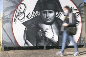 ?? Pascal Pochard-Casabianca / AFP via Getty Images ?? A woman walks by a billboard painted with the image of Napoleon Bonaparte in Ajaccio, a town on the island of Corsica, where Bonaparte was born in 1769.