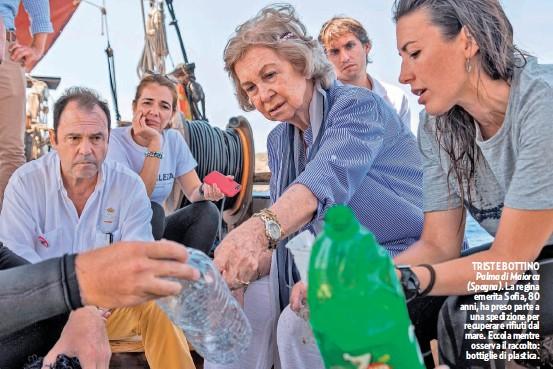 ??  ?? TRISTE BOTTINO Palma di Maiorca (Spagna). La regina emerita Sofia, 80 anni, ha preso parte a una spedizione per recuperare rifiuti dal mare. Eccola mentre osserva il raccolto: bottiglie di plastica.