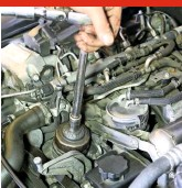 ??  ?? You'll need a spe­cial cup-type wrench to re­move the oil fil­ter cap, sit­u­ated just above the aux­il­iary drive­belt. Such wrenches are cheaply and read­ily avail­able. Put some old rags around the fil­ter hous­ing to ab­sorb any spillage, then undo the cap and re­move. You'll need to drain the oil next (see Step 22). 3 UNDO OIL FIL­TER