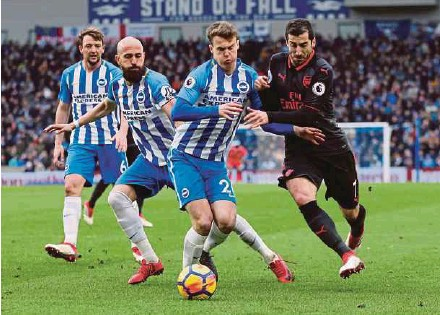 ?? REUTERS PIC ?? Arsenal's Henrikh Mkhitaryan (right) battles for the ball with Brighton's Solly March at The American Express Community Stadium yesterday.