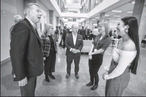 ?? Herald photo by Ian Martens ?? Canada Life's Paul Mahon, at left, alongside University of Manitoba Chancellor Anne Mahon and Power Corporation of Canada's Paul Genest, talk with biological sciences students Haley Allard and Haley Shade following a donation announcement in the Science Commons at the University of Lethbridge. @IMartensHerald
