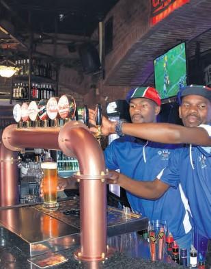 ??  ?? Barmen Simiso Makhanya and Nkanyiso Mabobo served customers in the Dros' new look bar Mari Scott