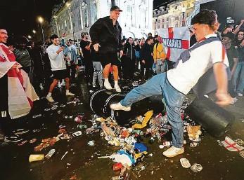 ?? Foto: ČTK ?? Vztek Angličtí fanoušci si po porážce svého týmu s Itálií vybíjejí frustraci na koších s odpadky.