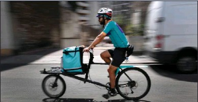 ?? Photo: NAMPA/AFP ?? The delivery guy… In this file photo taken in 2018, a biker working for the food delivery service, Deliveroo, cycles off to deliver an order in Saint-Ouen, outside Paris. The cyclists whisking meals for the food courier service Deliveroo in France called on clients to boycott the brand yesterday after management imposed new pay rules they say will lower their wages.