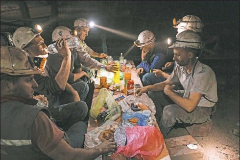 ?? (AP/Kemal Softic) ?? Bosnian coal miners break their fast in the underground at a mine in Zenica, Bosnia. Inside mine shafts, one can't see sunset, but miners consult their watches and smartphones for the right time to sit down, unwrap their food and break their daily fast together.