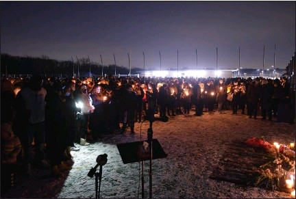 ?? PHOTOS BY MARK STOWERS — FOR ROYAL OAK TRIBUNE ?? A crowd of hundreds gathered at the stadium for Friday night's candlelight memorial ceremony.