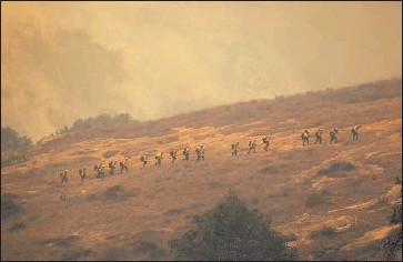 ?? Al Seib Los Angeles Times ?? FIREFIGHTERS from the California Conservation Corps get into position on the wind-driven Alisal fire in Santa Barbara on Tuesday afternoon. To the north, Pacific Gas and Electric warned of preventive outages.