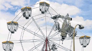 ?? Picture: REUTERS. ?? WILD RIDE: An ultralight plane crashed into a ferris wheel at a small town fair in Australia yesterday, narrowly missing two children, and dangled from the structure for more than an hour before its occupants could be rescued. Locals were stunned to...