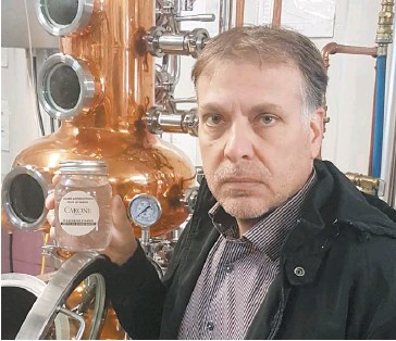 ?? PHOTO COURTOISIE VIGNOBLE CARONE ?? Le vigneron et distillateur Anthony Carone montre un bocal contenant du désinfectant pour les mains fait à partir de l'alcool produit dans son alambic.