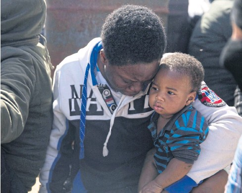 ?? AP ?? Migrants wait for medical attention on Wednesday in Tripoli. The Libyan coast guard returned about 500 migrants to Tripoli after an altercation with a volunteer rescue vessel.