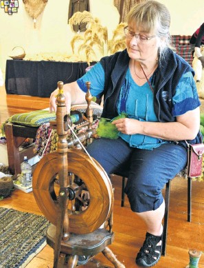 ?? PHOTOS: LINDA ROBERTSON ?? In a spin . . . Taieri Spinners and Weavers president Sarah Gamble spins some more yarn on her spinning wheel, affectionately know as Little Peggy, during the group's exhibition at the Dunedin Community Gallery.
