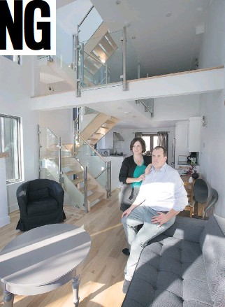 ?? PHOTOS: WAYNE CUDDINGTON/OTTAWA CITIZEN ?? The third-floor living room is a bright and cosy spot for owners Chantal Rioux and Nicolas Delahousse. Behind them are the stairwell, a rustic table that doubles as an at-home desk, and kitchen, while above is the 16-foot ceiling and loft. Not visible...