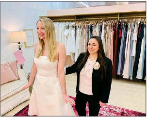 ?? (AP/Gilded Social) ?? Tanya Rutner Hartman, owner of Gilded Social, a bridal shop in Columbus, Ohio, helps a customer try on a gown earlier this month.