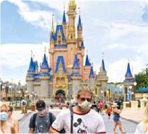 ??  ?? Gjester med munnbind i Disney World i Orlando, USA.