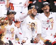 ??  ?? ARRIBA, Wade, James y Bosh celebran. A la derecha, LeBron James posa con los trofeos de JMV y de equipo campeón de la NBA. Abajo, Tony Parker, quien apenas se vio en el juego por los Spurs.