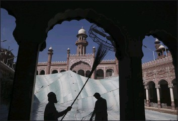 ?? MUHAMMAD SAJJAD — THE ASSOCIATED PRESS, FILE ?? Volunteers clean the outer areas of the historic Mohabat Khan Mosque ahead of the Muslim fasting month of Ramadan, in Peshawar, Pakistan, on April 9. Muslims are facing their second Ramadan in the shadow of the pandemic. Many Muslim majority countries have been hit by an intense new coronavirus wave. While some countries imposed new Ramadan restrictions, concern is high that the month's rituals could stoke a further surge.