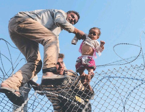 ??  ?? DESPERATE: A Syrian child is lifted over the wire near the Turkish border crossing at Akcakale. Picture: AFP